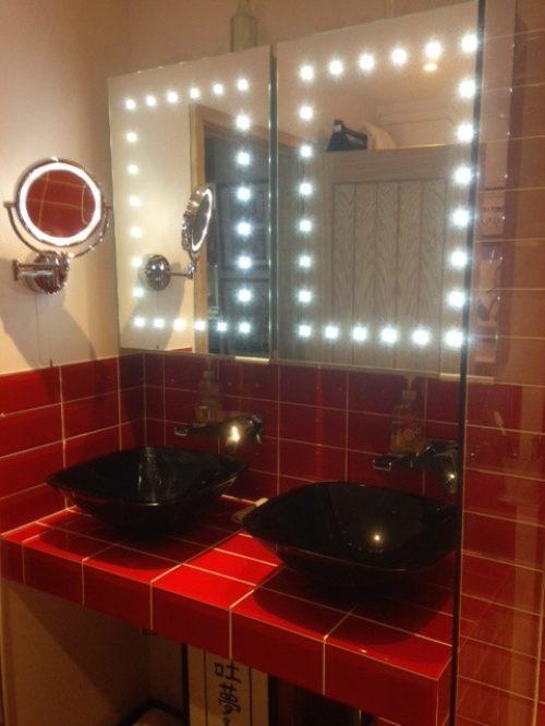pair of black wash basins on red tile vanity top