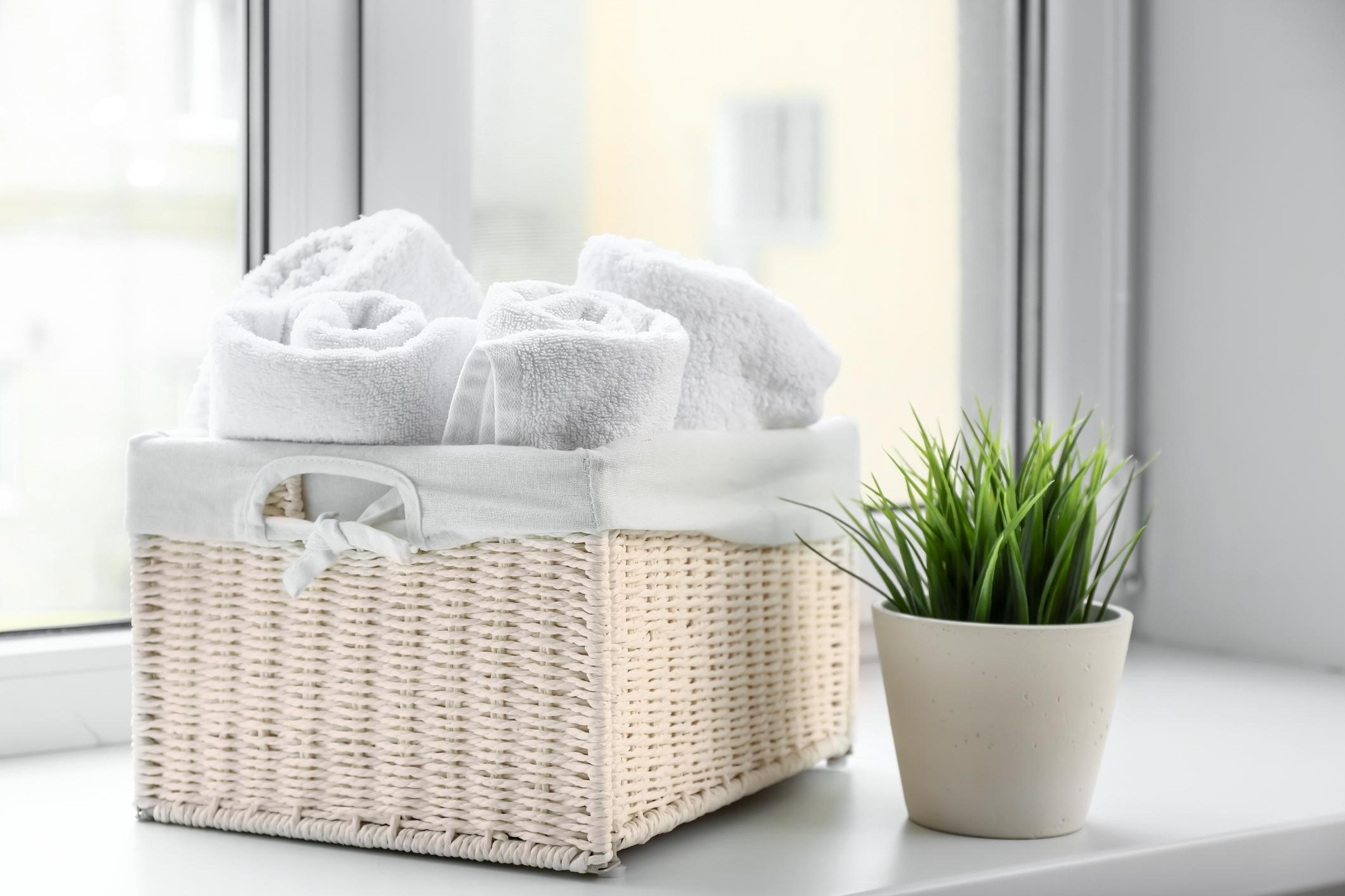 basket full of white towels on a window ledge with a green plant
