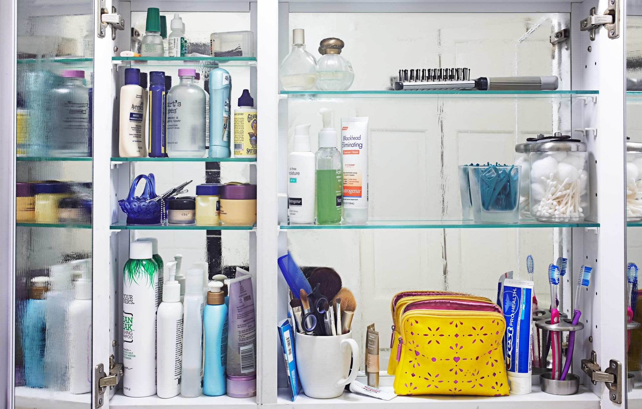 inside of a bathroom cabinet full of products, makeup brushes, toothbrushes and accessories